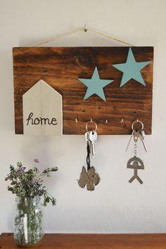 Cuadro decorativo elaborado con madera de palets con capacidad para colgar cinco juegos de llaves.