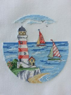 Lighthouse cross stitch work. Design by Maria Diaz. Sea, lighthouse and boats.