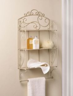 by Accent Plus Make your pretty things look even prettier by putting them on display with this gorgeous wall shelf. It features scrolling iron flourishes in ivory, three shelves, and a thin bar at the bottom for endless decoration possibilities.