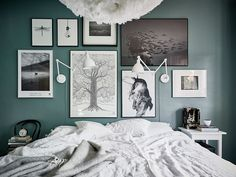 large picture wall on a painted dark green bedroom wall
