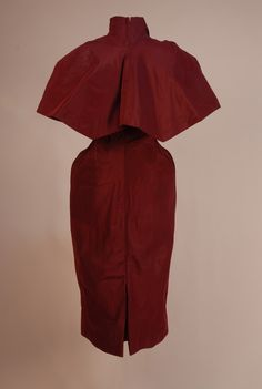 CHARLES JAMES COUTURE COCKTAIL DRESS and CAPELET, 1951, for ELEANOR SEARLE WHITNEY. Claret silk faille with boned satin corset bodice, pleated cap sleeve, breast insert and back neckline, arced waist, tulip skirt with kick pleat, back zip. Shoulder cape has pleats radiating from stand collar, short pointed lappets, back with two gentle points, double edge front inset with gold satin.