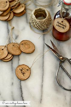 "Anthropologie inspired gift tags. --Diana of our vintage home love says, ""I knew these would be ridiculously easy to make so I went looking around in the backyard for a log, preferably a dead one that was already somewhat dried out.  I found the perfect one about 1 1/2 inches in diameter and used a miter saw to slice it into 1/4 inch slices.  I used a drill bit to make a small hole in the top and threaded a piece of twine through it.  Done."""