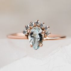A pear-shaped aquamarine adorned by a crown of CZ's and set in rose gold. Wear it alone or with an arched band to create a statement. Cubic zirconiaSterling silver rose gold plated x mm pear shaped aquamarine Prong band thickness Gold Diamond Rings, Halo Diamond, Rose Gold Rings, Black Diamond, Simple Jewelry, Fine Jewelry, Plain Gold Ring, Aquamarin Ring, Rose Gold Jewelry