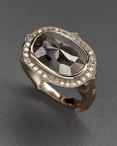 oval rough cut diamond with brilliant cut pave diamonds surrounding.