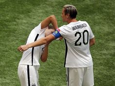 Carli Lloyd gives the captain's armband to Abby Wambach