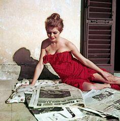 Die französische Schauspielerin Brigitte Bardot liest, nur eingehüllt in eine rote Fransendecke, auf einer Terrasse die Tageszeitungen. (undatierte Aufnahme)