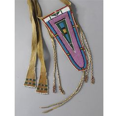 A CROW BEADED HIDE BELT POUCH composed of hide, wool cloth, glass beads, sinew and cotton thread.  Length of beaded flap 11 in.