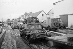 Aktiv Fischer Snow Trac ST4 in a convoy of British military vehicles drives along a muddy road in Port Stanley, during the Falkland Islands War