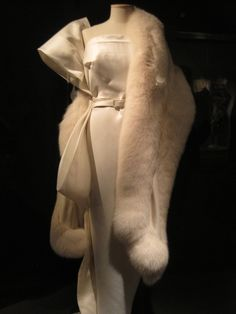 "Marilyn's white satin evening gown worn to the premier of ""Call Me Madame"" in 1953. This gown was designed by William Travilla and is identical to the pink 'Diamonds Are A Girl's Best Friend"" gown."