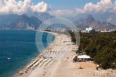 The view on the city beach in Antalya, Turkey. The beach is surrounded by mountains which are covered with white clouds.