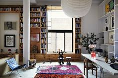 Inez and Vindooh New York Loft   Floor to ceiling bookshelf, printed rugs and mis-matched pieces