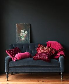 Charcoal wall and sofa is striking when paired with bright cushions.