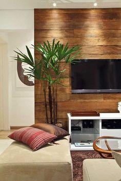 aqui o painel de madeira foi valorizado com a iluminação. Traz um ambiente moderno e aconchegante.: