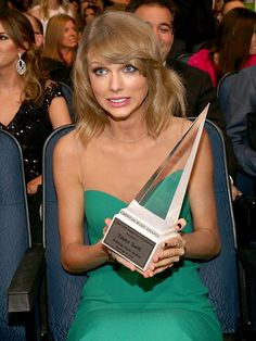 Taylor Swift holding on to her Dick Clark Award for Excellence at the AMAs