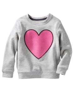 Featuring a soft French terry blend and one happy heart, this pullover keeps her style comfy and sweet.