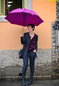 Guarda chuva lilás, casaco longo cinza com detalhes em pedrarias nos braços, calça preta encerada, body preto com margaridas rosas, bota preta de bico quadrado e salto