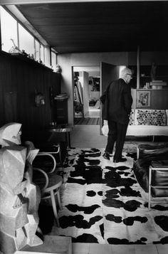 """Magnum Photos - Rene Burri Apartment-atelier Le Corbusier (1931-1934). France. Paris. 16th. 24, rue Nungesser-et-Coli. Moving through the flat, Le Corbusier shows pieces from his collection. Left: Jacques LIPCHITZ's sculpture """"Marin à la guitare"""" from 1917."""