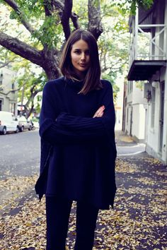 A chic navy jumper is worn with black trousers.