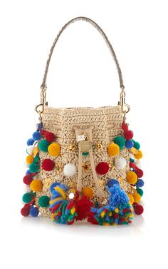 This Spring Summer 16 collection is rife with Sicilian references, manifested in spring's elaborate Renaissance emblems, majolica ceramic heels, and pom-pom embellishments. This bucket bag by **Dolce & Gabbana** features multiple colorful pompoms, a long over the shoulder stap and a drawstring closure.