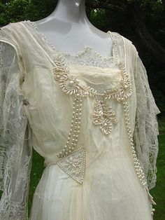 Bodice of a circa 1915 wedding gown of white silk satin, white floral lace, and chiffon, and trimmed with pearl beads.