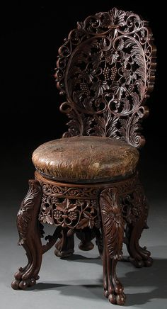 A CONTINENTAL CARVED WALNUT PIANO STOOL late 19th century, of adjustable height, with screw turned leather seat, allover pierced scrolling grape leaf and fruit carved cluster back above a seat raised on four claw footed legs. Jackson's International Auctioneers and Appraisers