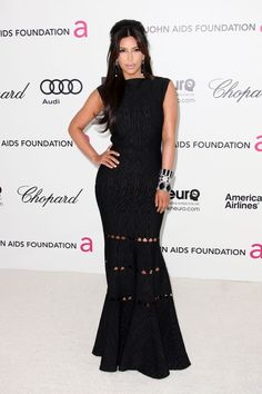 Kim Kardashian kept things demure at Elton John's Oscar viewing party in a black figure-hugging gown with peekaboo cut-outs
