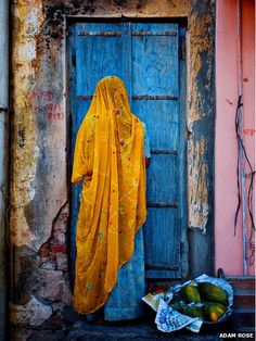 A woman dressed in traditional garb returns home from a street market. Photo by Adam Rose, BBC News in pictures