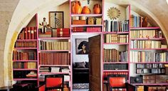 Bookshelves constructed inside a stone archway and edged in bright pink.
