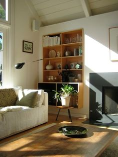 Built in library shelving in the living room. Tucked away and the perfect amount! Black fireplace and mcm room.
