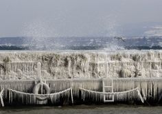 Waves hit an ice covered wall on a windy winter day in the harbour of Versoix near Geneva February 3, 2012