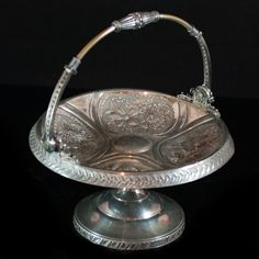 """Lot #94: Rogers & Bro. Silverplated Compote  DESCRIPTION: Rogers & Bro, triple silver plated handled compote. Features ornate floral designs along the center bowl and reed adornment along the circumferance. Finished with an elgantly designed swiveling handle. Marked: """"Rogers & Bro. Triple Plate 1927″  CIRCA:20th Ct. ORIGIN:USA DIMENSIONS:H: 5: (With Handle): H:11″ Diameter:8.5″"""