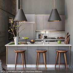 Eine rold gerahmte Küchenzeile wirkt neben dunklen Farbtönen sehr edel und dennoch modern. Das Thema wird auch in den dunklen Hängeleuchten geschickt …