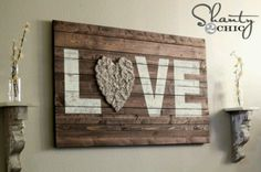 DIY Wood Wall Art I needed something fun to hang above my couch. I used some scrap wood to make a sign that would fit the space perfectly. I stenciled LOVE and added some rosettes! It was cheap and so easy. You can see the full tutorial at