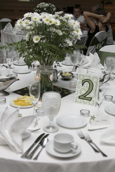 DIY wedding table decor @ Norfolk Marriott. White & green:  I made the table numbers, the place cards, the favors, and the centerpieces ($tree vase decorated with tulle & ribbon placed on a mirror).  Also used paper punched flowers on the white linens.