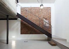 Black metal stairway with brick wall. Features with Flos Aim pendant light. U V House by O A S I architects. Photo by Stefania Matteo.