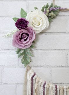 The Julia Dream Catcher is a beautiful, dusty lavender accented piece. She is made of a light wooden 12in ring, which hangs an array of white and cream colored yarn, ribbon and lace. She also has dusty lavender colored yarn to accent the matching flowers. The flower accents are white and lavender, along with sage colored greenery. Chic and classic, this piece is perfect for a wedding, an event or home decor. The total length of Aphrodite from top to bottom is 36in and the total width is…