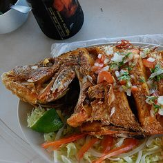 "Fried fish is one of the favorite foods from the Yucatecan coast. In this particular case, this is a boquinete accompanied by lettuce, and drizzled with a sauce called ""xnipec"" (known as ""pico de gallo"" in other parts of Mexico), made ​​from chunks of tomato, onion, chili and cilantro."