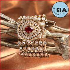 Sia Reverse American Diamond Stones Bracelet. A masterly crafted Bracelet with Reverse American Diamond Studded stones. This bracelet has beautiful pear shape in center with a Ruby stone Studded and oval shape stones which is giving it a Mughal Era Jewellery look.
