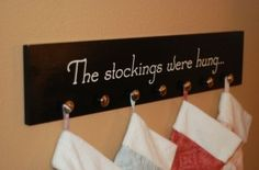 Great DIY Idea:  Stocking holder wall plaque.  1 - Buy wooden board.  2 - Paint board or Mod Podge craft paper on.  3 - Screw in knobs.  4 by sara