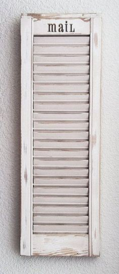 Got an old shutter laying around? Sand it down to give it this distressed look, then use it as a mail sorter!