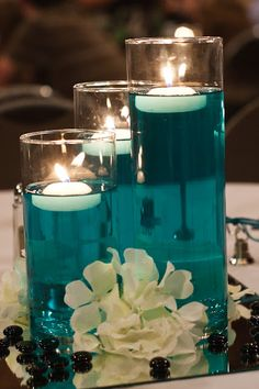 """A little bit of food color & water with some floating candles. Cylinders from dollar store. I like that we can bring in the """"tiffany blue"""" color with the orange flowers and white candles"""