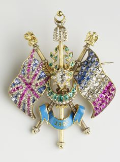 The 'Alliance Flag' brooch, 1855, made using silver, gold, rubies, sapphires, diamonds, emeralds and enamel by John Linnit; comprises the crossed flags of Britain and France with a central laurel wreath (symbol of victory) and a star and crescent (symbol of Turkey); the brooch celebrates the British alliance with France and Turkey in the Crimean War; it was commissioned as a gift from Prince Albert to Queen Victoria. (Royal Collection Trust/© Her Majesty Queen Elizabeth II 2014)