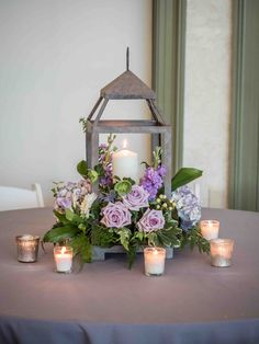 Simple and elegant rustic center piece using a wooden lantern and beautiful purple flowers! Candles give an extra warmth to the centerpiece.   Charlotte wedding, Charlotte wedding vendors, NC wedding, NC wedding vendors, Outdoor, purple, garden wedding   Venue @stowegarden @ballantynehotel Planner @somethingperf Catering @bicaterers
