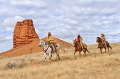 600-08082918© Martin RuegnerModel Release: YesProperty Release: YesCowboy and Cowgirls Riding Horses with Castel Rock in the background, Shell, Wyoming, USA