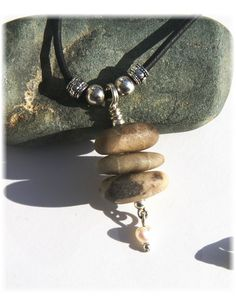 Stacked Petoskey Stones suspended on a leather cord {Sterling Silver bail} along with a fresh water pearl as a dangle. Sterling Silver hook and eye closure.