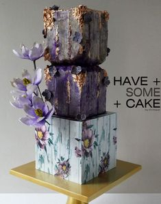 Pretty purple shades and sugar flowers balance the natural, mineral shapes of the top gold detailed tiers, while the bottom tier looks like rustic painted wood. Amazing Wedding Cakes, Unique Wedding Cakes, Unique Cakes, Wedding Cake Designs, Amazing Cakes, Gorgeous Cakes, Pretty Cakes, Cute Cakes, Purple Cakes