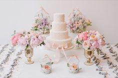 Bolo de casamento ao centro, com acessórios de flores: resultado delicado e romântico em tons pastéis
