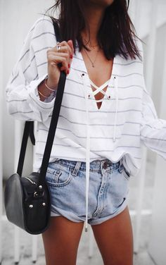 Casual summer outfit idea. Oversized stripped sweater with white wash denim jeans and a bkack satchel bag.