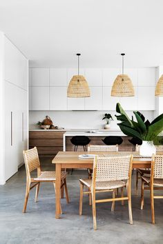 Rattan dining chairs and pendant lights with timber dining table and concrete floors next to open plan white kitchen. New Builds, Home, Rattan Dining Chairs, Timber Dining Table, Interior, Home And Family, Indoor Outdoor Living, Home Decor, Room Interior