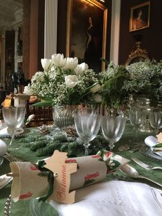 Carolyne Roehm - sage green theme, using juniper and baby's-breath, flanked by silver vases with white tulips nestled in a ring of greens